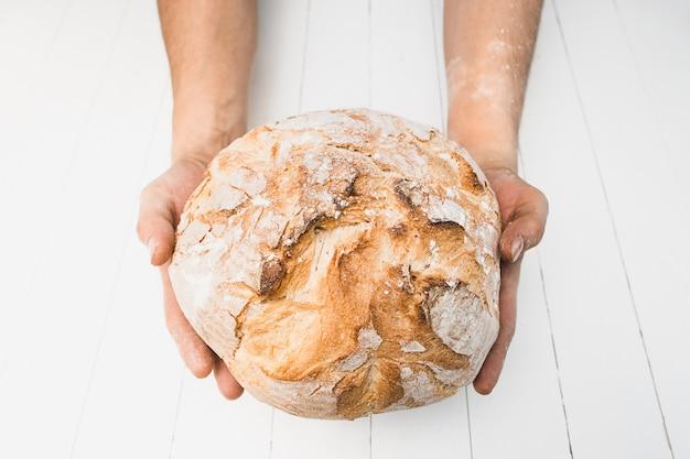 Крупным планом мужской руки положить свежий хлеб на старый деревенский стол на черном фоне с копией пространства для вашего текста Бесплатные Фотографии