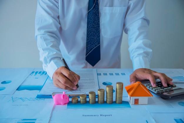 Макрофотография нового домовладельца, подписывая договор продажи дома или ипотечных бумаг с деревянным игрушечным домом Premium Фотографии