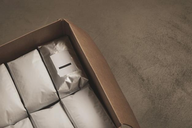Крупным планом открытая большая картонная коробка, полная белых пакетов Бесплатные Фотографии