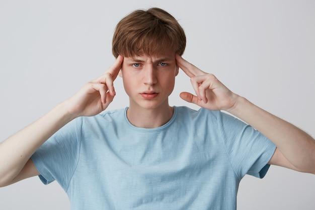 Крупным планом задумчивый напряженный молодой человек носит синюю футболку, касается его висков, думает и имеет головную боль, изолированную над белой стеной Бесплатные Фотографии