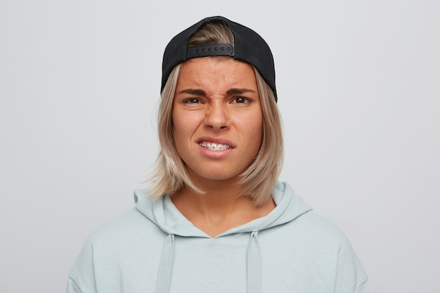 歯にブレースを付けた悲しい不幸な金髪の若い女性のクローズアップは黒い帽子をかぶっていて、パーカーは白い壁の上に孤立して動揺し、不機嫌そうに見えます 無料写真