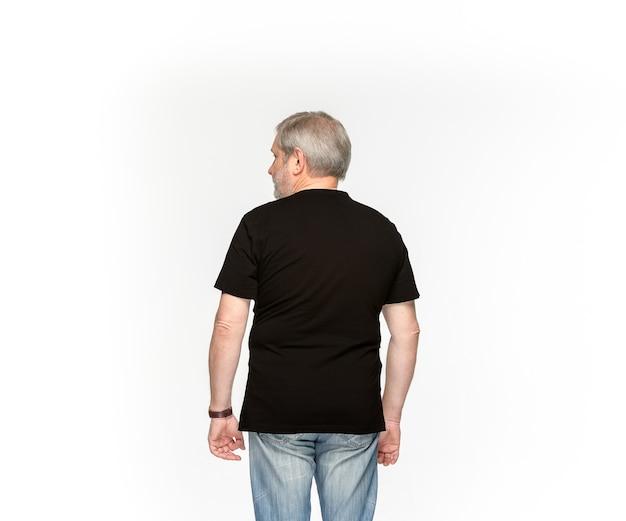 白で隔離される空の黒いtシャツで年配の男性の体のクローズアップ。 無料写真