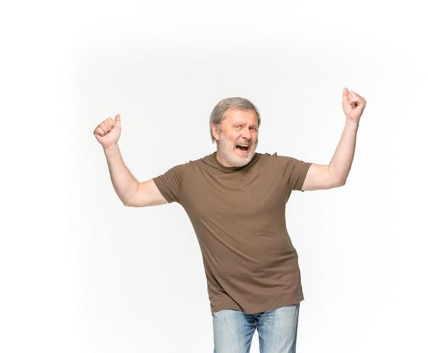 白で隔離される空の茶色のtシャツで年配の男性の体のクローズアップ。 無料写真
