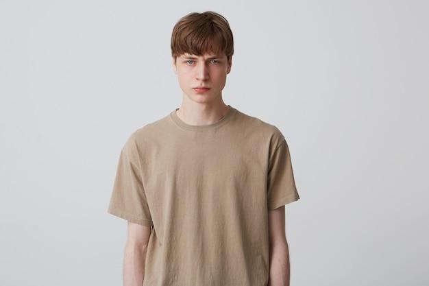 Крупным планом серьезный сердитый молодой человек в бежевой футболке стоит, чувствует себя расстроенным и смотрит вперед, изолированно от белой стены Бесплатные Фотографии