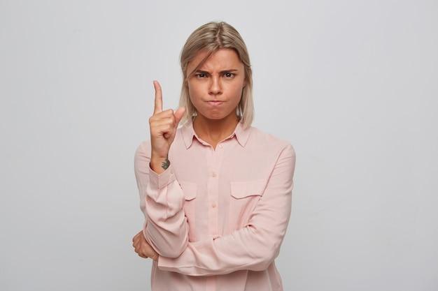 Крупным планом серьезная строгая блондинка молодая женщина в розовой рубашке выглядит подчеркнутой и указывает вверх пальцем, изолированным над белой стеной Бесплатные Фотографии