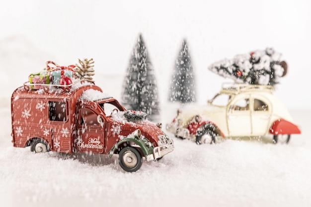 Крупным планом маленькие автомобильные игрушки на искусственном снегу с небольшими елками на заднем плане Бесплатные Фотографии