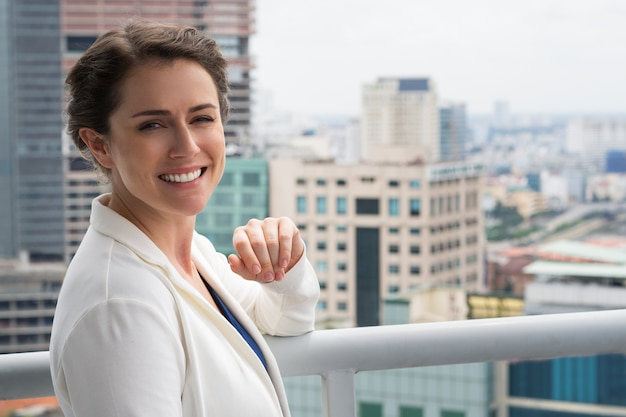 Closeup of Smiling Adult Businesswoman on Balcony Free Photo