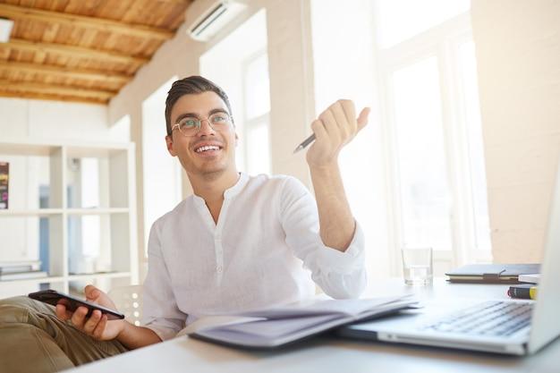 Крупным планом улыбающийся привлекательный молодой бизнесмен носит белую рубашку в офисе Бесплатные Фотографии