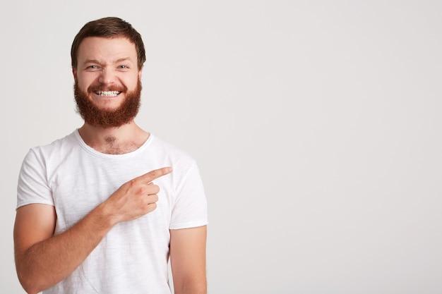 笑顔の魅力的な若い男のヒップスターのひげを生やしたtシャツを着てのクローズアップは幸せを感じ、白い壁に隔離された指でコピースペースの側を指しています 無料写真