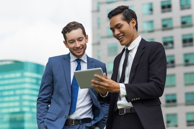 Closeup of Smiling Coworkers Using Tablet Outdoors Free Photo