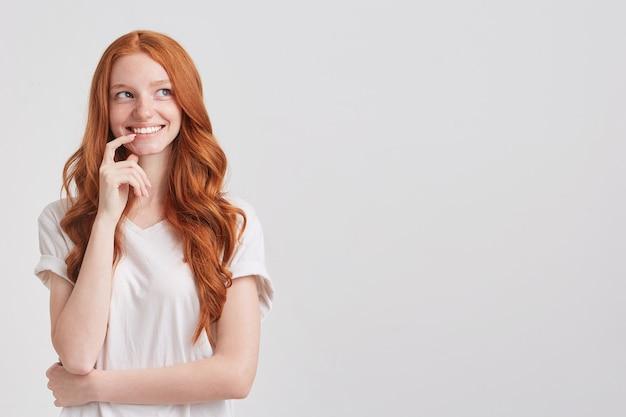 Крупным планом улыбающаяся прекрасная рыжая молодая женщина с длинными волнистыми волосами Бесплатные Фотографии