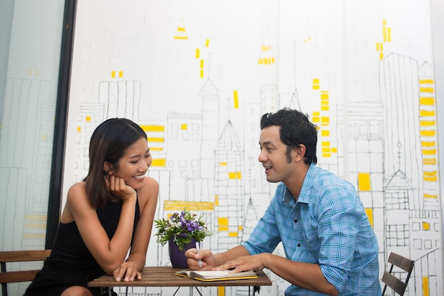 Closeup of Smiling Young Couple Sitting in Cafe Free Photo