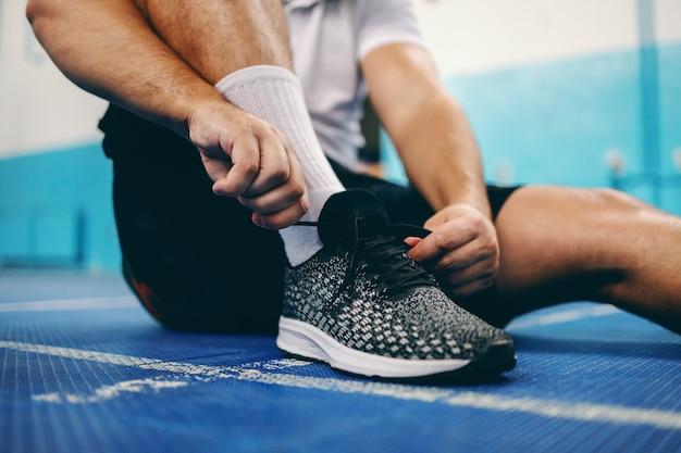 スポーツホールに座っている間靴ひもを結ぶスポーツ選手のクローズアップ。 Premium写真