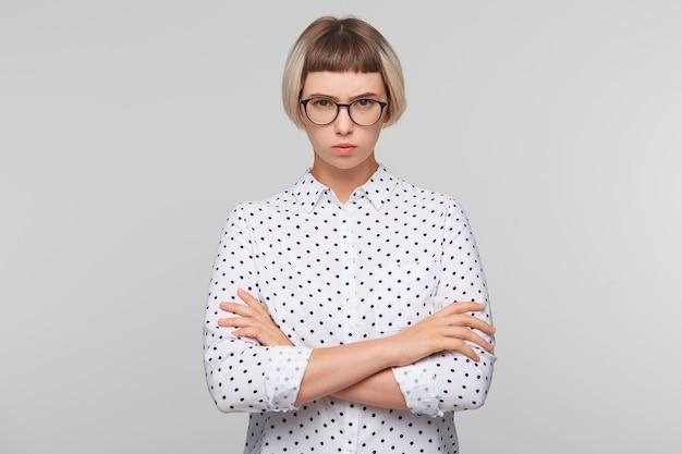Крупным планом задумчивая довольно блондинка молодая женщина носит рубашку в горошек Бесплатные Фотографии
