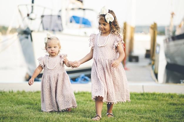 항구 근처를 걷고 비슷한 드레스에 두 귀여운 아기 소녀의 근접 촬영 무료 사진