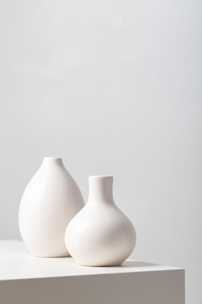 Крупным планом две белые глиняные вазы на столе под огнями на белом Бесплатные Фотографии