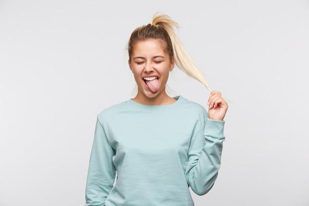 Крупным планом несчастная симпатичная молодая женщина со светлыми волосами и хвостиком носит синюю футболку Бесплатные Фотографии