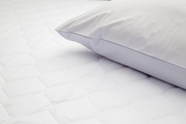 寝室のベッドの上に白い枕のクローズアップ Premium写真