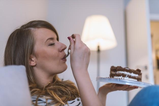 Devojka jede tortu sa uživanjem