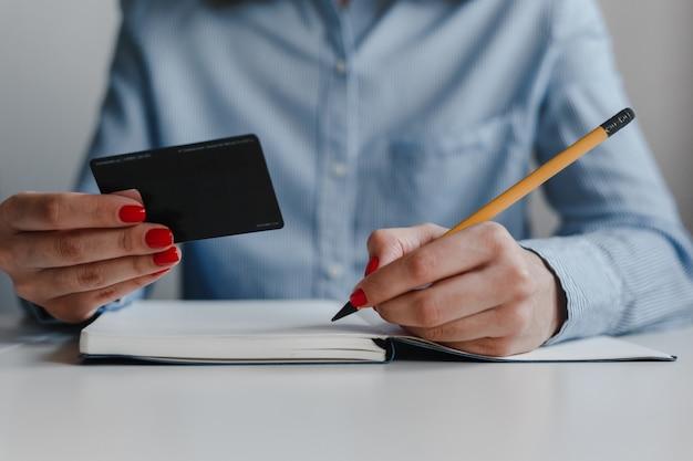 Крупным планом женская рука с красными ногтями писать в тетради желтым карандашом и носить синюю рубашку кредитной карты. Premium Фотографии