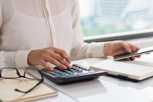 Макрофотография женщина, используя калькулятор и смартфон Бесплатные Фотографии