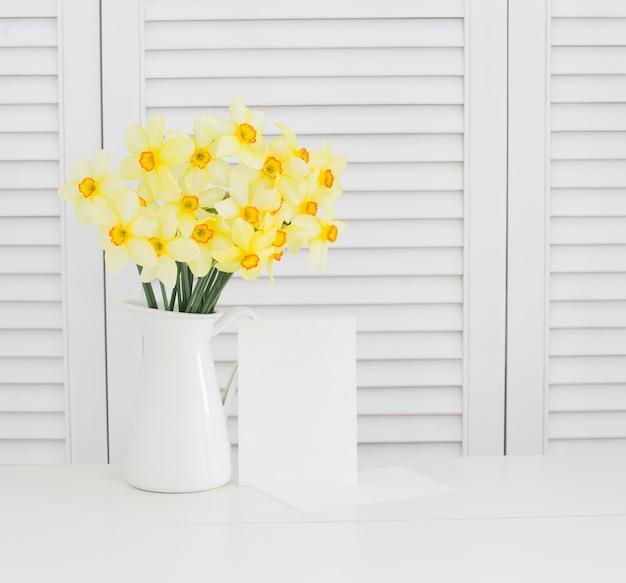 白いシャッターの上の花瓶に黄色い水仙の花のクローズアップ。きれいなプロヴァンス風の装飾 無料写真