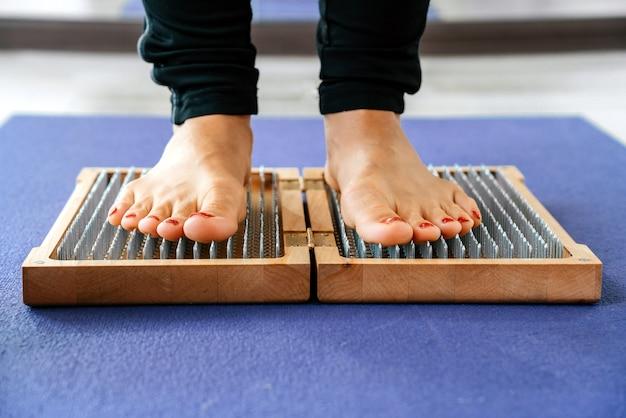 Крупным планом человека йоги, стоящего на доске садху с острыми гвоздями Premium Фотографии