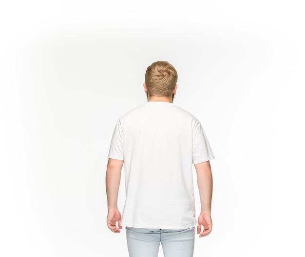 白で隔離される空の白いtシャツで若い男の体のクローズアップ。 無料写真