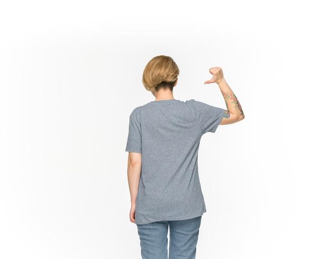 白で隔離される空の灰色のtシャツの若い女性の体のクローズアップ。 無料写真