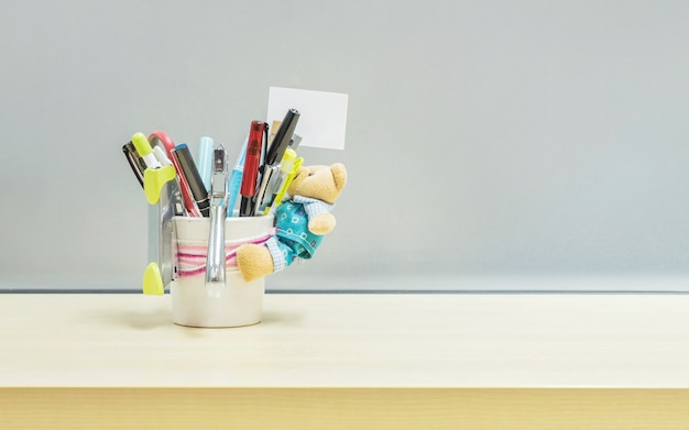 Closeup office equipment in desk tidy cup on desk Premium Photo