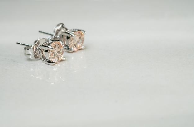 Крупным планом старые серьги с бриллиантами на размытом фоне мраморного пола Premium Фотографии