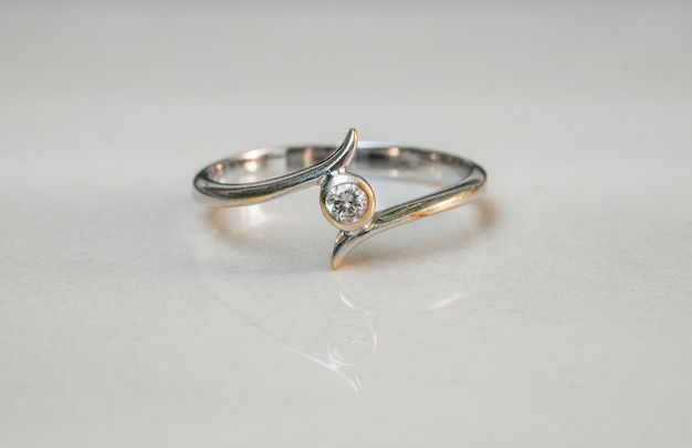 Closeup old diamond ring on blurred marble floor background Premium Photo