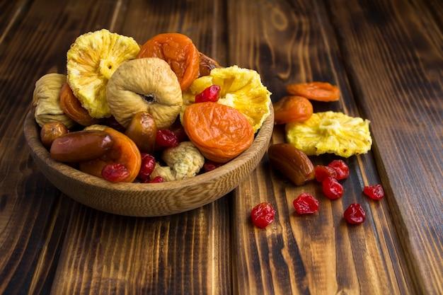 木製のテーブルの茶色の弓のさまざまなドライフルーツのクローズアップ Premium写真