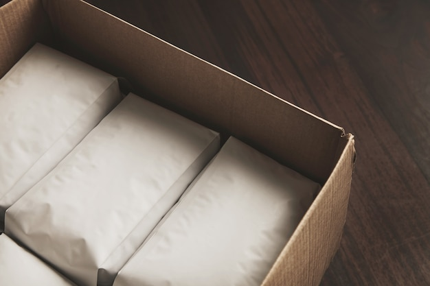 Closeup opened big carton box full of blank hermetic white packages with coffee or tea Free Photo