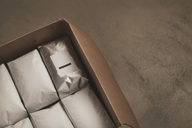 Closeup of opened big carton box full of white packages Free Photo