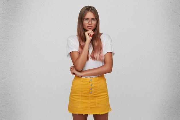 Il primo piano della giovane donna attraente pensierosa indossa la maglietta, la gonna gialla e gli occhiali tiene le mani piegate e pensa isolato sopra il muro bianco Foto Gratuite