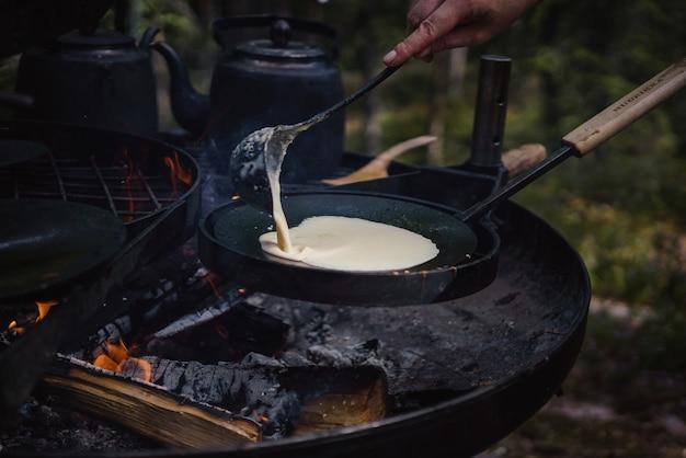 Primo piano di una persona che cucina frittelle sul fuoco all'aperto Foto Gratuite