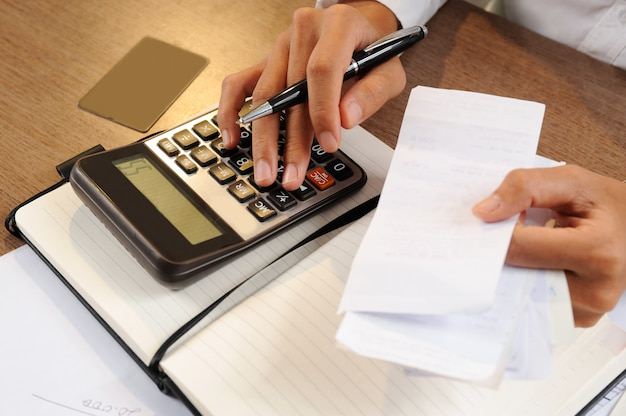 Closeup of person holding bills and calculating them Free Photo