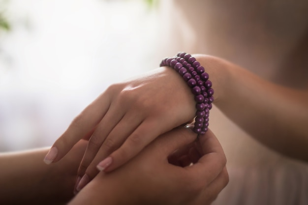 Closeup of a person putting a purple bracelet around the hand of a woman under the lights Free Photo