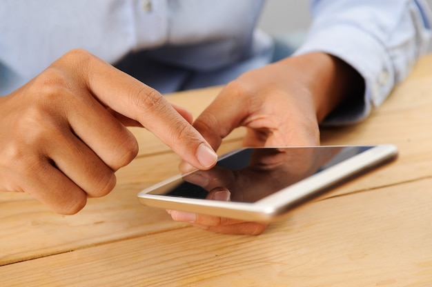 Closeup of person using smartphone at table Free Photo
