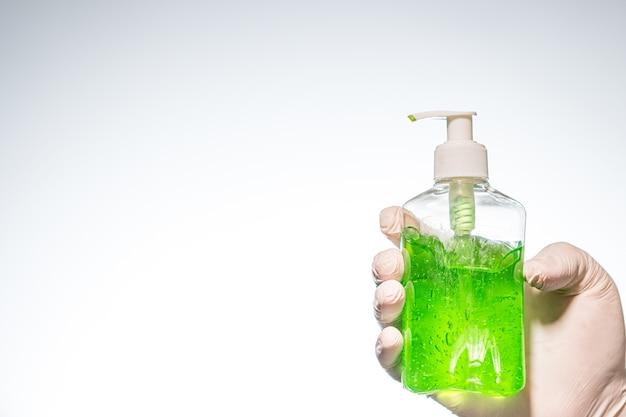 Primo piano di una persona con un guanto di lattice che tiene un disinfettante per le mani verde sotto le luci Foto Gratuite