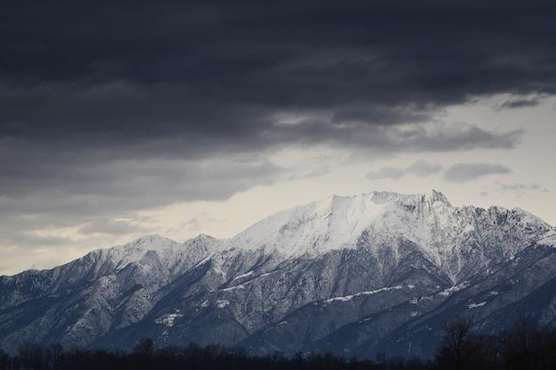 Primo piano pf montagne innevate delle alpi con nuvole scure Foto Gratuite