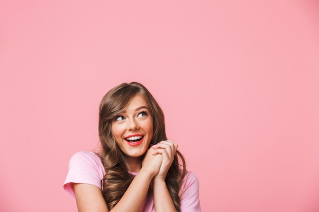 Closeup photo of joyful pretty woman with long curly brown hair looking aside at copyspace and holding hands together in rejoice, isolated over pink background Premium Photo