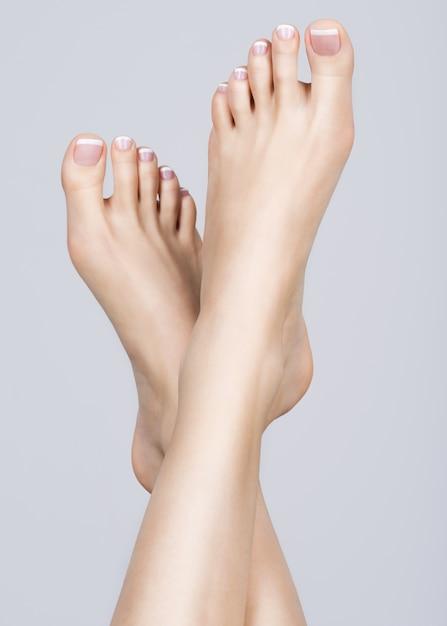 Крупным планом фото женских ног с белым французским педикюром на ногтях Бесплатные Фотографии