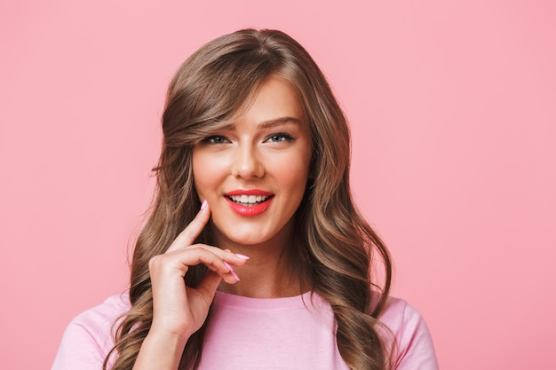 ピンクの背景に分離されたあなたを見ながら笑みを浮かべて長い巻き毛の茶色の髪を持つ愛らしいコンテンツ女性のクローズアップ写真 Premium写真