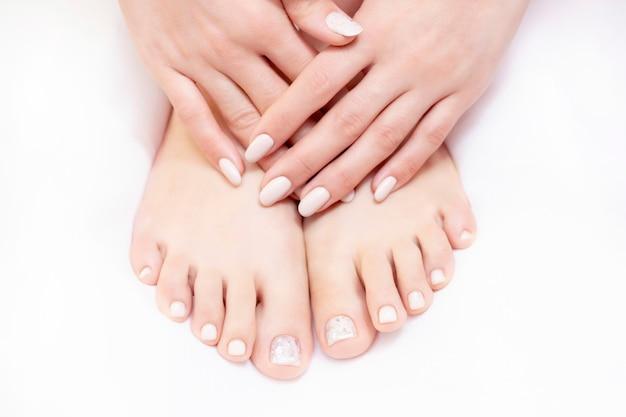 ペディキュアとマニキュアの手順にスパサロンで白いタオルに女性の足のクローズアップ写真。ヌードカラー。 Premium写真