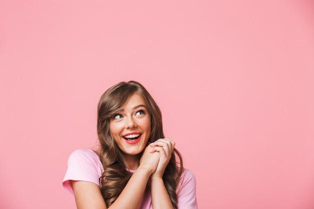 ピンクの背景に分離されたcopyspaceをよそ見と一緒に喜んで手を繋いでいる長い巻き毛の茶色の髪とうれしそうなきれいな女性のクローズアップ写真 Premium写真