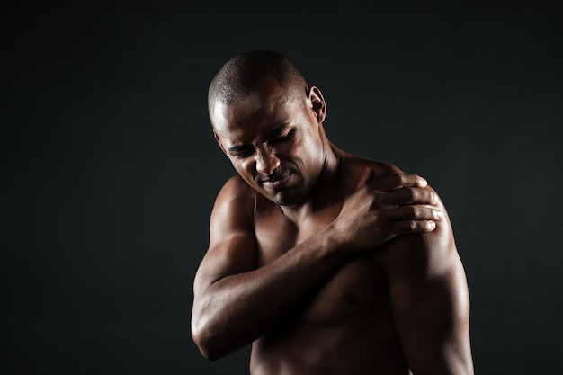 Closeup photo of young shirtless afro american man with shoulder pain Free Photo