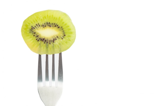 Closeup of a piece of kiwi on fork with copy space on white background Free Photo