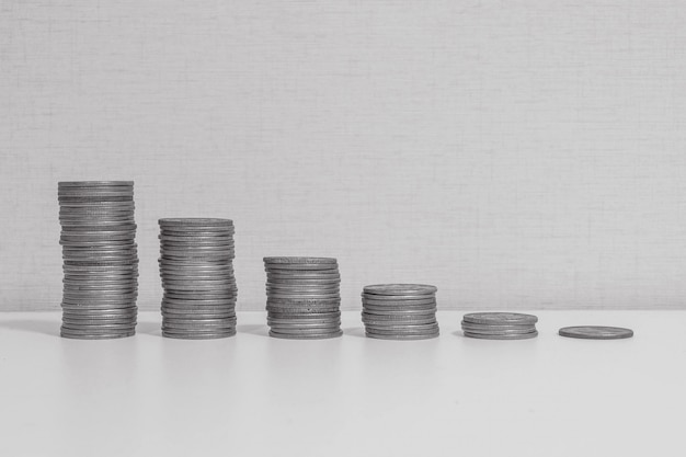 Closeup pile of coin start from high to low on wood desk Premium Photo